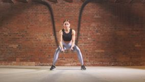 Caucasian fit woman exercising with battle ropes at gym. stock footage