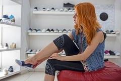 Caucasian flicka för härlig rödhårig man som väljer och bär nya skor i lagret arkivfoto