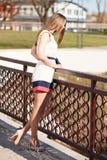 Caucasian flicka i den vita klänningen och höga häl på bron Royaltyfri Bild