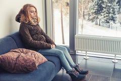 Caucasian flicka i varm kläder som sitter på den blåa soffan royaltyfria bilder
