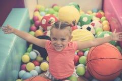 Caucasian flicka med öppna armar som sitter på kulör boll liten gi arkivfoton