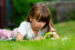 Caucasian flicka med förstoringsglaset Arkivfoto