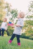 Caucasian flicka- och pojkebarn som vinkar amerikanska flaggan parkerar in, utvändigt fira 4th juli, självständighetsdagen Fotografering för Bildbyråer