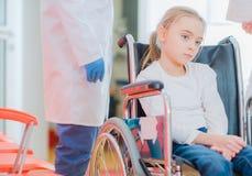 Caucasian flicka på en rullstol royaltyfria bilder