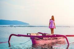 Caucasian flicka som poserar anseende på ett rosa fartyg i havet på solnedgången på ön av Gili arkivfoton