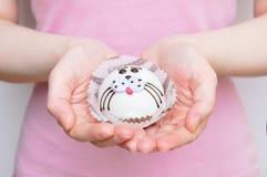 Caucasian flicka som rymmer en muffin arkivfoton