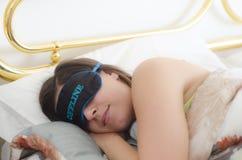 Caucasian flicka som sover i sängen med en maskering på henne ögon och t royaltyfri fotografi