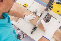 Caucasian Flooring Contractor. At Work Cutting Piece of Laminate Panel Using Circular Table Saw stock image