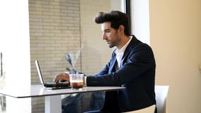 Businessman sitting in cafe, drinking fresh coffee typing with his laptop. stock footage