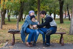 Caucasian fun family: dad, mom and their son are sitting on a bench in the Park in autumn stock photo