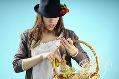 Caucasian girl arranging easter ornaments. Teenager girl with black hat arranging easter ornaments in basket Stock Photography