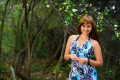 Caucasian girl in blue dress posing in forest in summer Stock Images