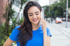 Caucasian girl with blue shirt speaking at phone in the city Royalty Free Stock Image