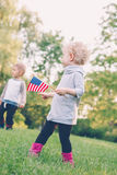 Caucasian girl and boy children waving American flag in park outside celebrating 4th july, Independence Day Stock Image