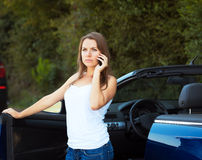 Caucasian girl on a cell phone service or tow truck traffic near Stock Images