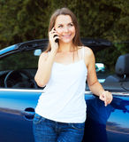Caucasian girl on a cell phone service or tow truck traffic near Stock Photos