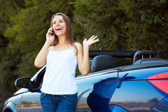 Caucasian girl on a cell phone service or tow truck traffic near Stock Photography