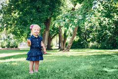 Caucasian girl child in blue dress standing in field meadow park outside Stock Photos