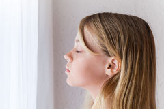 Caucasian girl with closed eyes near a window Stock Photo