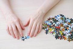 Caucasian girl collects puzzles on table. View from above stock images