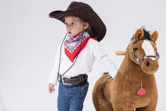 Caucasian Girl in Cowgirl Clothing Posing With Symbolic Plush Horse Against White. Stock Photo