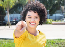 Caucasian girl with curly black hair pointing at camera. Outdoor in a city in south america in the summer Royalty Free Stock Photos