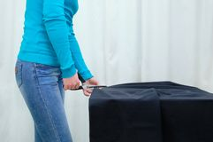 Caucasian girl cuts black fabric on table. In room royalty free stock images