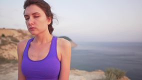 Caucasian girl doing breathing practice - meditation in the morning by the ocean, closeup view. 4k stock footage
