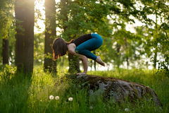 Caucasian girl doing yoga in city park. B. Young caucasian brunette girl doing balance yoga asana in nature outdoor forest. Bakasana Stock Photography