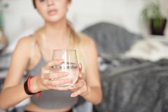 Caucasian girl drinks water sitting on the bed in the morning royalty free stock photo