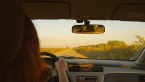 Caucasian girl drive car by shaky country road. Rural landscape. Sunset evening in autumn. White girl driving car vintage style. Golden sunset stock video