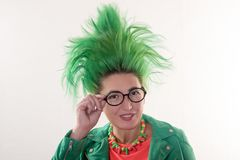 A caucasian girl in a green dress and with green hair is preparing for the holidays. Suit of the teacher of primary classes. The c. Oncept of happy holidays and Stock Photos