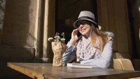 Girl Chats in Outdoor Cafe. Caucasian girl, in grey striped hat and coloured scarf, chatting on the phone in outdoor cafe, slowmotion on sunny autumn day stock footage