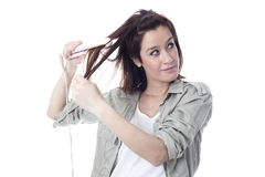 Caucasian girl with hair iron Stock Photo