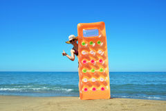 Caucasian girl with hat and inflatable mattress on the beach. Royalty Free Stock Image