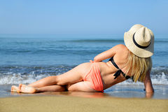 Caucasian girl with hat lying on the beach. Stock Photo