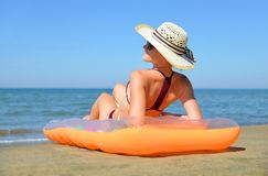 Caucasian girl with hat lying on inflatable mattress on the beach. Stock Image