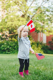Caucasian girl holding and waving American flag in park outside celebrating 4th july Independence Day Flag Day concept Stock Photo