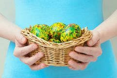 Caucasian girl holds in her hands basket with Easter painted yellow eggs. Close-up. Caucasian girl holds in her hands a basket with Easter painted yellow eggs stock images