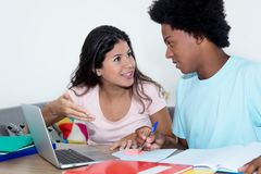Caucasian girl learning with african american male student. At desk at home Royalty Free Stock Photography