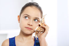 Caucasian girl listening to the noise of shells Stock Photo