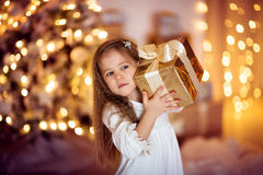 Caucasian girl with long hair Christmas gift, golden lights, bo. Caucasian girl with long hair with a Christmas gift, golden lights, the concept of the New Year stock images