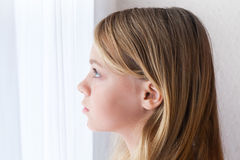Caucasian girl looking in a window with white curtains. Closeup profile portrait of beautiful blond Caucasian girl looking in a window with white curtains Stock Photos