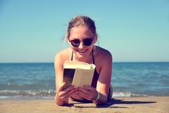 Caucasian girl lying on beach and reading a book. Royalty Free Stock Photography