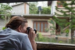 Caucasian girl making photos from train window while treavelling in Sri Lanka. royalty free stock photo