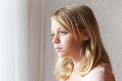 Caucasian girl near a window with white curtains Stock Photo