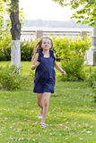 Caucasian girl run in summer with disheveled hair. Cute running European girl with disheveled hair in summer royalty free stock image