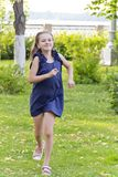 Caucasian girl run in summer with disheveled hair. Cute running European girl with disheveled hair in green park royalty free stock image