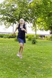 Caucasian girl run in summer with disheveled hair. Cute running European girl with disheveled hair in green park royalty free stock photos