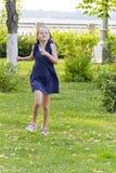 Caucasian girl run in summer with disheveled hair. Vertical photo of cute running European girl with disheveled hair stock image